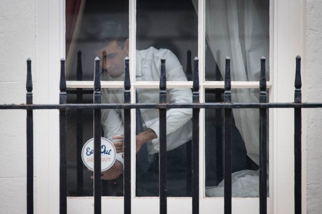 Chancellor Rishi Sunak places an 'Eat out to help out' sticker in the window of No.11 Downing Street in London, ahead of the new scheme encouraging customers to return to the hospitality industry. The initiative will provide up to ??10 off meals to diners eating out every Monday, Tuesday and Wednesday during August at participating businesses across the UK. PA Photo. Picture date: Thursday July 16, 2020. See PA story HEALTH Coronavirus. Photo credit should read: Stefan Rousseau/PA Wire
