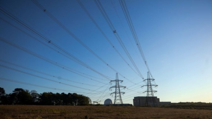 Electricity transmission pylons stand in front of Sizewell A, right, and B, left, nuclear power stations, operated by Electricite de France SA (EDF), stand in Sizewell, U.K., on Friday, May 15, 2020. The network operator struck a deal with EDF??to cut supply at its??Sizewell??nuclear plant by half for at least six weeks because the demand for power is 20% lower than normal as measures to contain the coronavirus have shut industry and kept people at home for weeks. Photographer: Chris Ratcliffe/Bloomberg via Getty Images