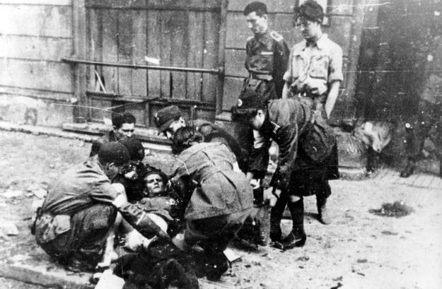 Powstanie warszawskie. Udzielanie pomocy rannemu na ulicy /Z archiwum Narodowego Archiwum Cyfrowego