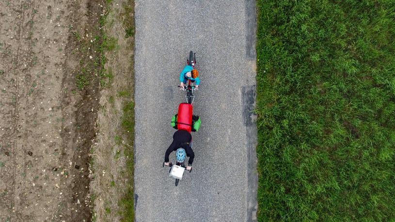 Rower dziecka holowany przez rodzica, zdjęcie autorstwa Kuby Ruty zrobione na Gościńcu Mirowskim, Szlak Orlich Gniazd w trakcie rowerowego wyjazdu z dziećmi /dzieciakiwplecaki.pl /archiwum prywatne