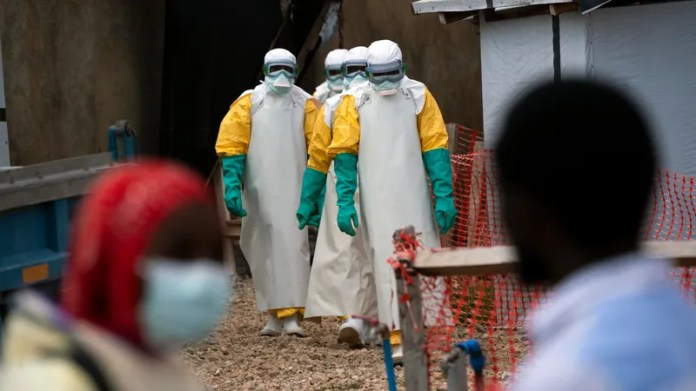 Health workers in protective gear start their shift at an Ebola treatment center in Beni, Congo DRC.