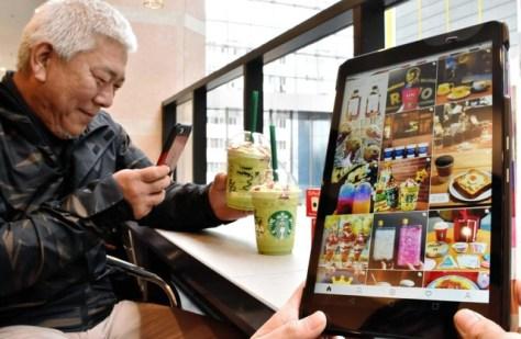 インスタグラム用にフラペチーノを撮影する下村光三さん=神戸市中央区