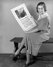 woman holding a poster showing FDR's Mother's Day stamp
