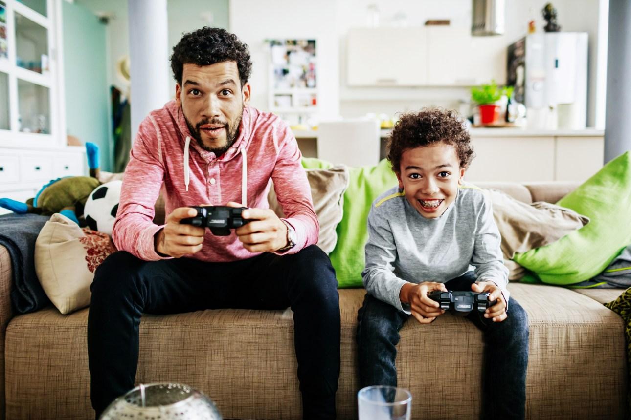 мужчина и ребенок на диване с контроллерами видеоигр, глядя на телевизор