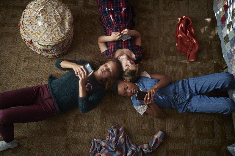 3 kids lying on the floor looking at their phones