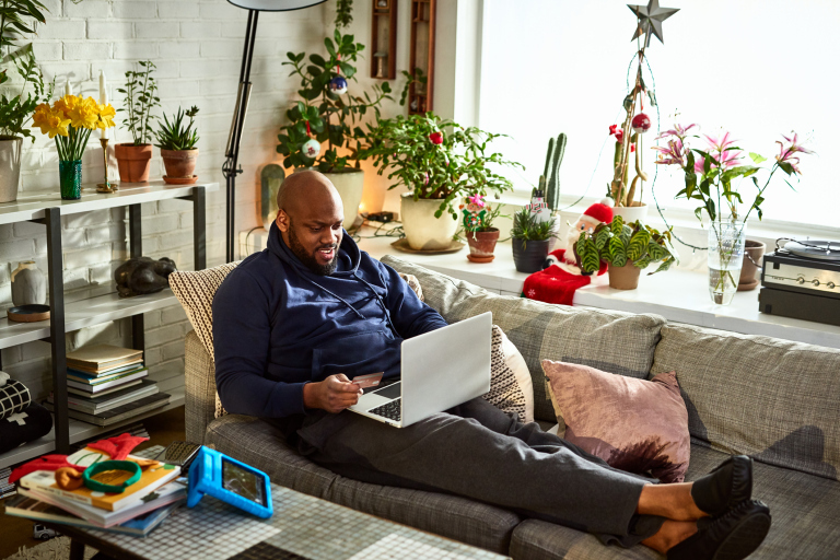 guy sitting on his couch with his feet up, looking at his laptop
