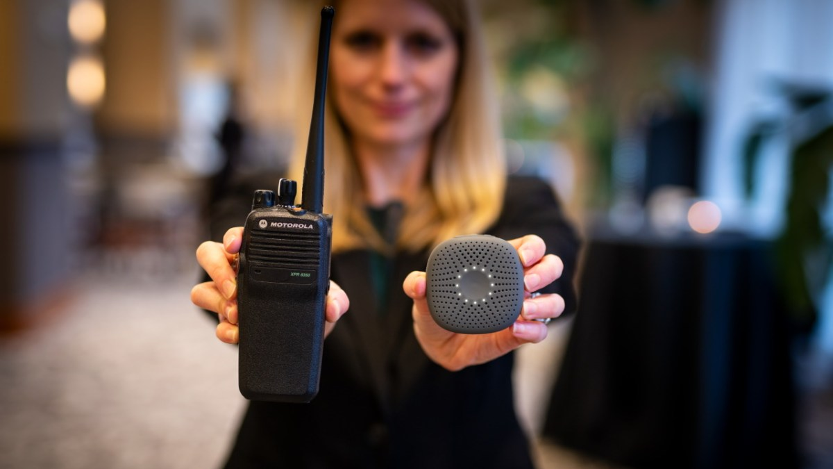 A person holding a walkie-talkie and a Relay+