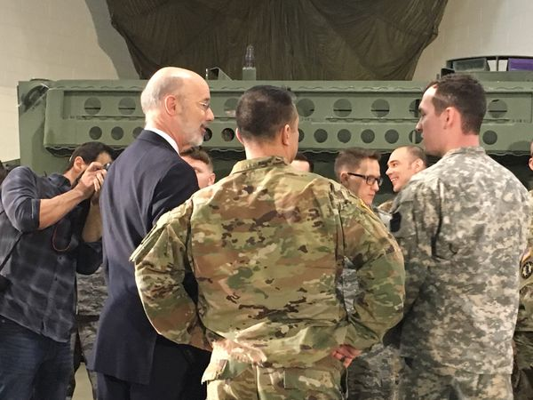 Prior to discussing a proposed education program to benefit military families, Gov. Tom Wolf (at left in suit) spent some time talking with the Pennsylvania National Guard members in attendance at a news conference on the first-of-its-kind program.