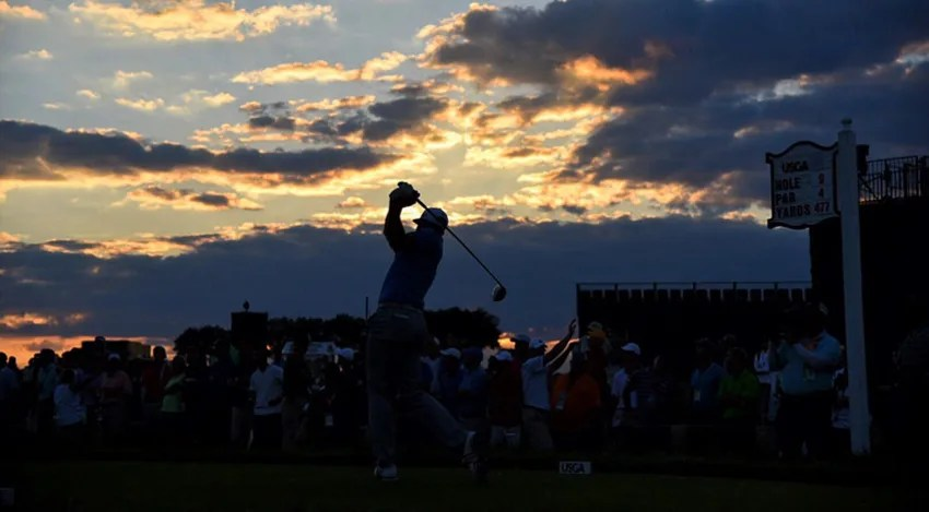 Dustin Johnson tees off on the ninth hole, his 36th hole of the day, as the sun sets in the distance. (Keyur Khamar/PGA TOUR)