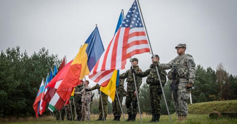 """Valami magyar cikkíró eldicsekedett azzal, hogy nekünk milyen gazdag harci tapasztalataink vannak a NATO-val. Azért az ukránok sem ültek ölbe tett kézzel az évek során. Nagyon sok NATO hadgyakorlaton vesznek részt, a Lvov megyei (Galícia) Jaroviv lőtér gyakorlatilag a NATO rendelkezésére áll. Egész évben, zászlóaljak váltásával folyik az ukrán katonák ki-, illetve továbbképzése. Nagy amerikai haditengerészeti támaszpont-komplexum épül a Fekete-tenger északnyugati szögletében, az Ogyesszától északkeletre fekvő OCSAKOV várossal a központban, a Krím hátában, attól mindössze 150 km-re. Évről évre Ogyessza mellett zajlik a NATO """"Sea Breeze"""" nevű hadgyakorlata, természetesen ukrán részvétellel. Gyakorlatilag folyamatos, szabad bejárást kaptak Ukrajna területére, korlátlanul, egész évre, évenkénti formális meghosszabbításokkal. Beregszászra (a határunktól 10 km-re) egy felderítő-diverzáns zászlóaljat telepítenek, amelynek rendszeres továbbképzését brit kiképzők végzik majd. A képen elölről a második az ukrán zászló - az amerikai és román zászló között, az amerikai takarásában."""