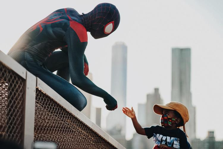 spiderman and a kid at a protest