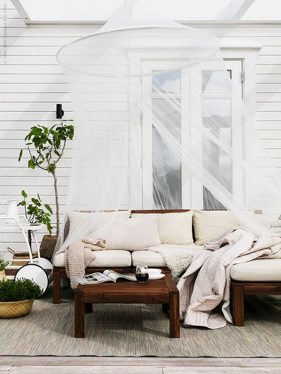 a stained wooden sofa with neutral cushions and pillows for a chic look (you can even use it as a small dining area)
