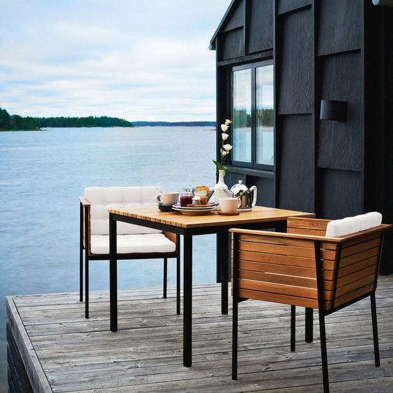 simple wooden upholstered chairs and a small table on a deck to take them inside easily