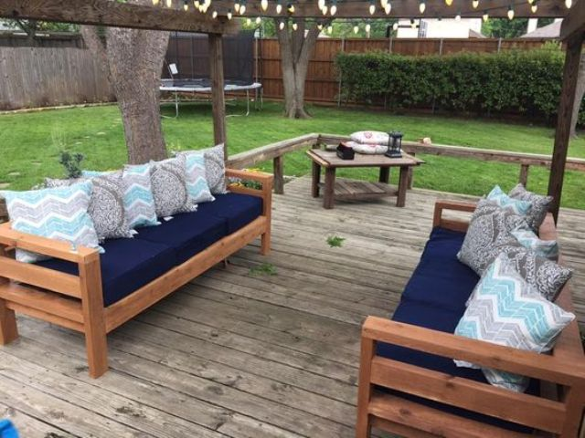 stained wood sofas with navy cushions and patterned pillows