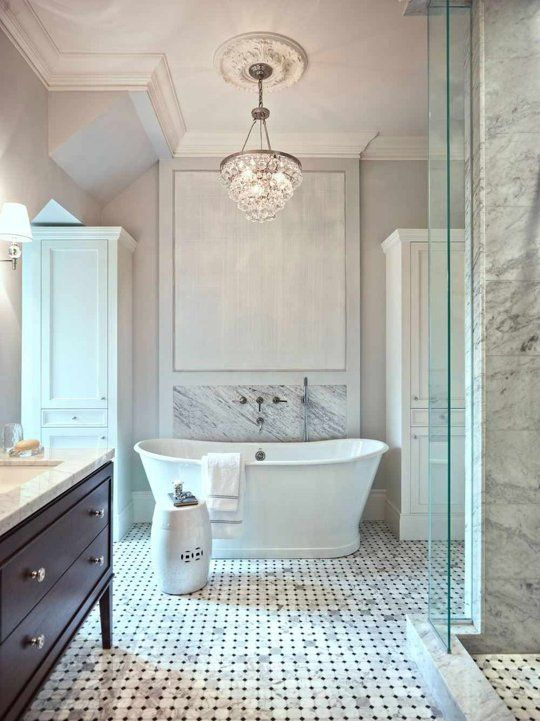 A Refined Marble Bathroom With Crystal Chandelier Accentuated Ceiling Medallion