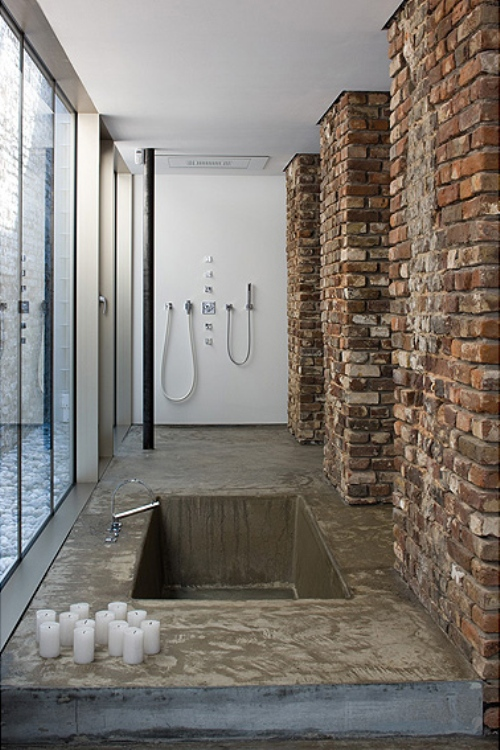 Bare brick works well with concrete in this shower design.
