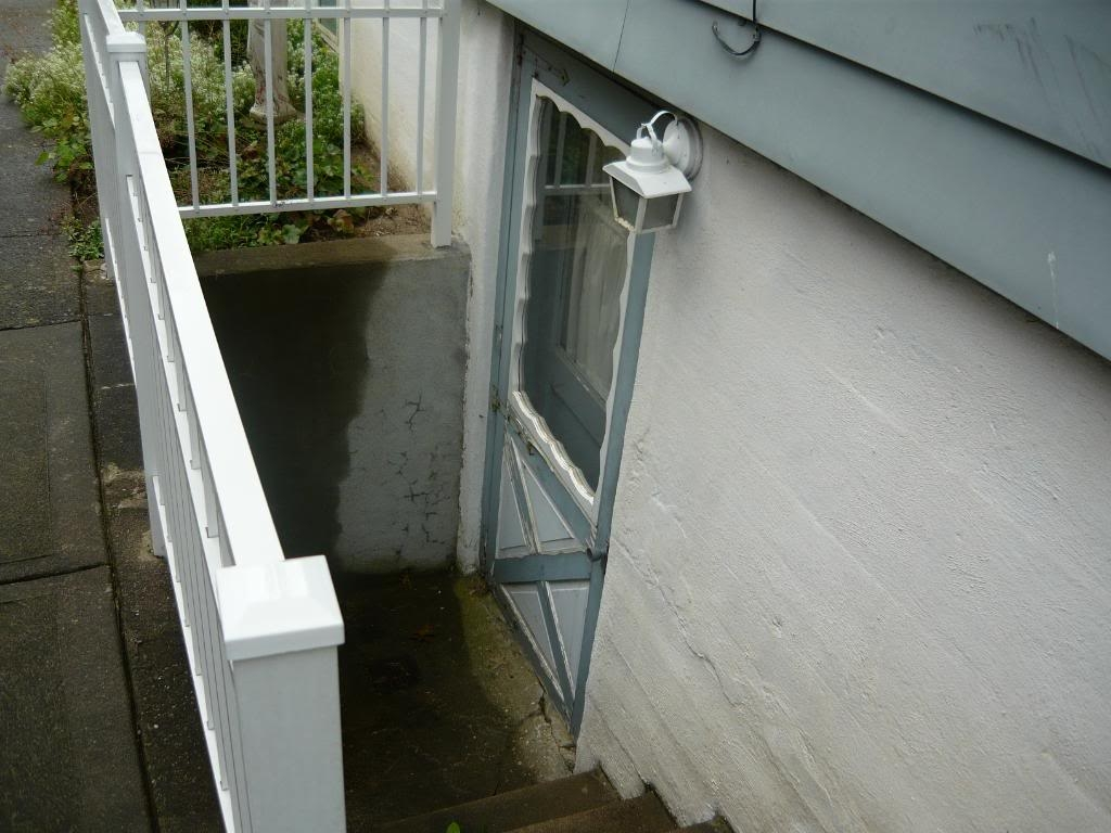 Preventing Clogging Flooding At Bottom Of Exterior Basement Steps | Stairs Leading To Basement | Beautiful | Painted | Unfinished Basement | Metal | Basement Peaked Roof