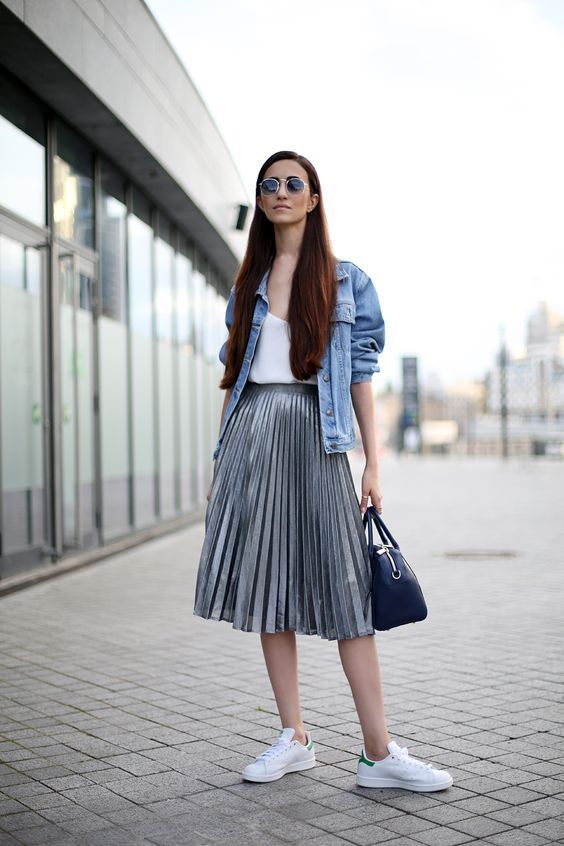 a white top, a grey pleated midi skirt, a blue denim jacket and white sneakers for a rock feel