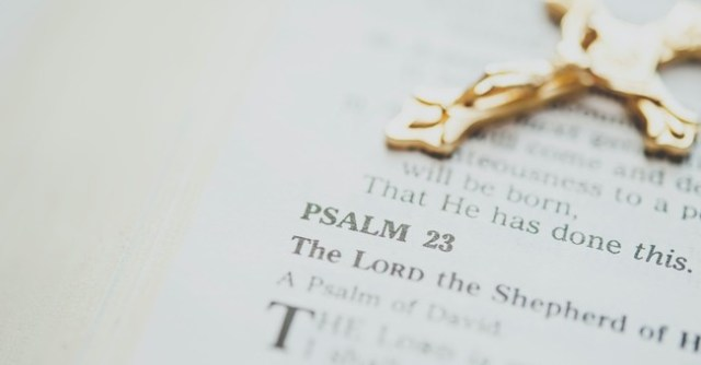 Bible opened to Psalm with a cross