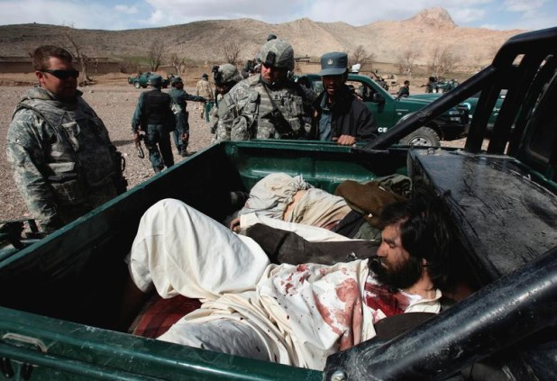 US Army soldiers and an Afghan policeman look at the bodies of Taliban fighters after a 40-minute gun battle near the village of Shajoy in Zabol province March 22, 2008. [Photo: Reuters]