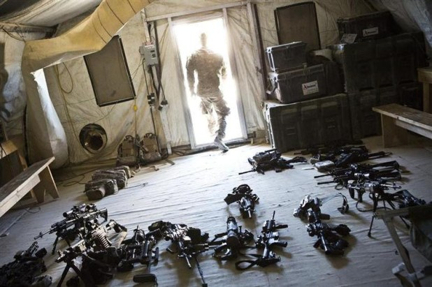 A soldier from 1st Platoon, Alpha Company, 1st Battalion, 36th Infantry leaves a room while checking the inventory of weapons at Strong Point DeMaiwand, Maywand District, Kandahar Province, Afghanistan, January 20, 2013. [Photo: Reuters]