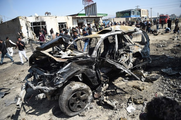 Afghan security personnel and civilians gather next to a damaged car at the site of a car bomb attack in Kabul on March 17, 2018. [Photo: AFP]