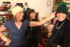 Janet League-Katzin, left, and her daughters Helena Greene, right, and Michelle League-Thornton try on some hats in Helena's shop, Swing, in Harlem in New York.