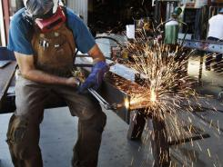 In this July 1, 2011 photo, John Rosas, an employee with the metal works factory Wizard of Metals, cuts steel in San Francisco.
