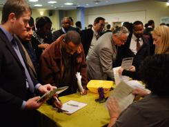 Job seekers speak with employers at the New York Career Fair at a midtown Holiday Inn Oct. 24, 2011.