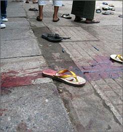 Blood soaked sandals are shown on a street following a shooting by soldiers during a protest in downtown Rangoon on Thursday.
