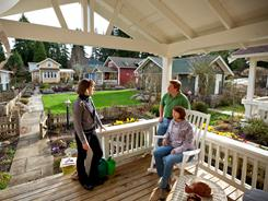Brian and Colleen Ducey, right, chat with neighbor Eileen McMackin on their front porch in Shoreline, Wash., where eight bungalows share a yard, garden and commons building.