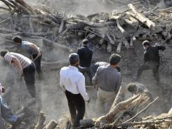 Iranians search the ruins of buildings after Saturday's earthquake.