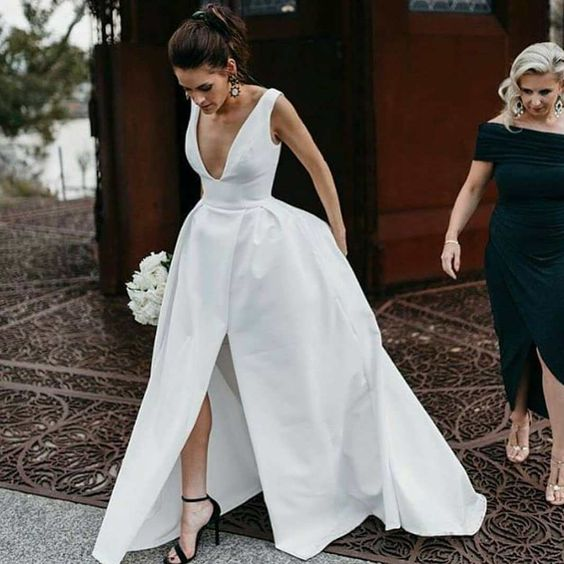 a structural white wedding gown with a front split and black ankle strap shoes for a minimalist look