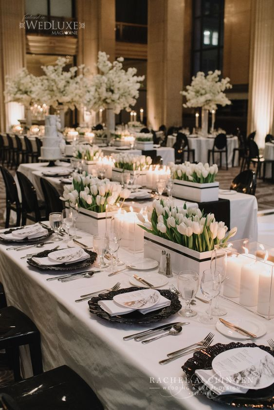 a stylish wedding tablescape with black chargers, white tulips in boxes and a white tablecloth