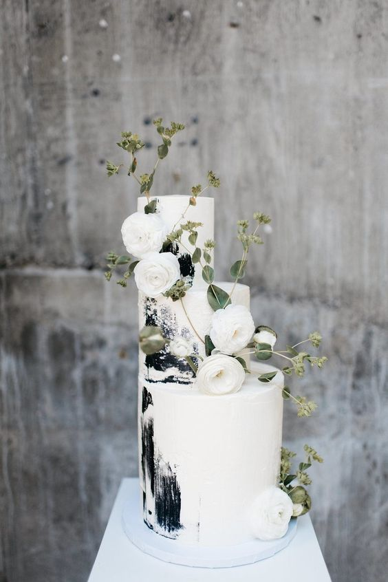 a white wedding cake with black brushstrokes and white ranunculus and greenery