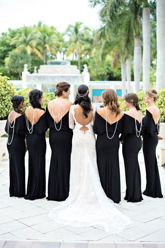 the bridesmaids wearing black maxi dresses with pearl statement necklaces and the bride wearing white