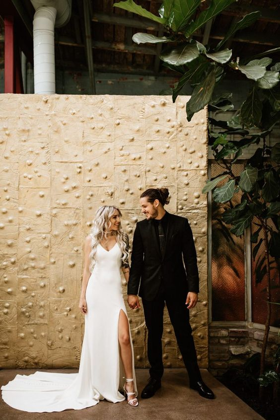 the groom in a total black outfit, the bride wearing a total white outfit with a minimalist feel