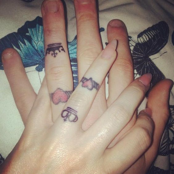 Double wedding ring tattoos of hearts and crowns is a cool idea for two