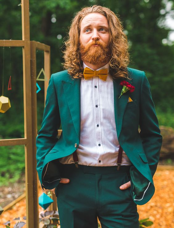 an emerald suit, a white shirt with black buttons, suspenders and a mustard bow tie to pull off a jewel color palette