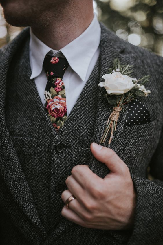 a grey tweed three-piece suit, a white button down and a moody floral tie plus a floral boutonniere