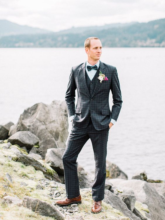a retro groom's look with a navy windowpane print suit in three pieces, an aqua shirt, a blue bow tie and brown shoes
