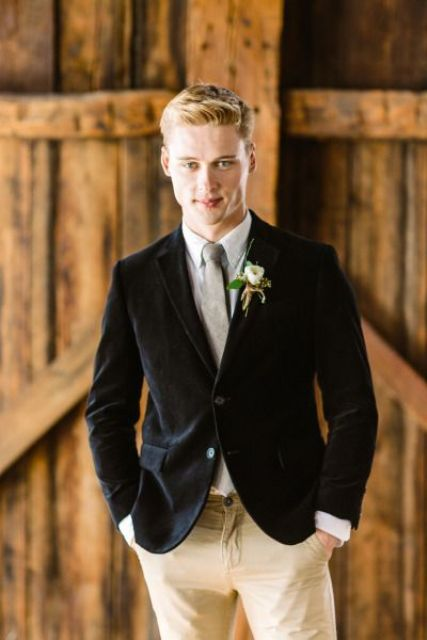 a vintage-inspired groom's look with tan pants, a neutral shirt, a grey tie and a black velvet blazer