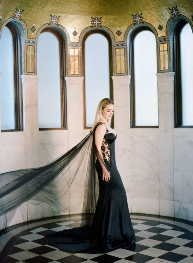 a black mermaid wedding dress with lace inserts on the sides and a long cape