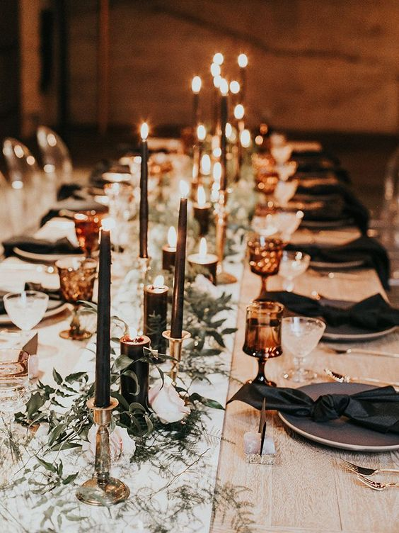 a chic gothic wedding tablescape with a neutral runner, black napkins, black candles and subtle greenery