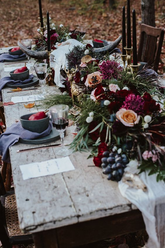 a gothic forest tablescape with an uncovered table, grey plates and chargers, lush blooms and greenery plus berries and black candles