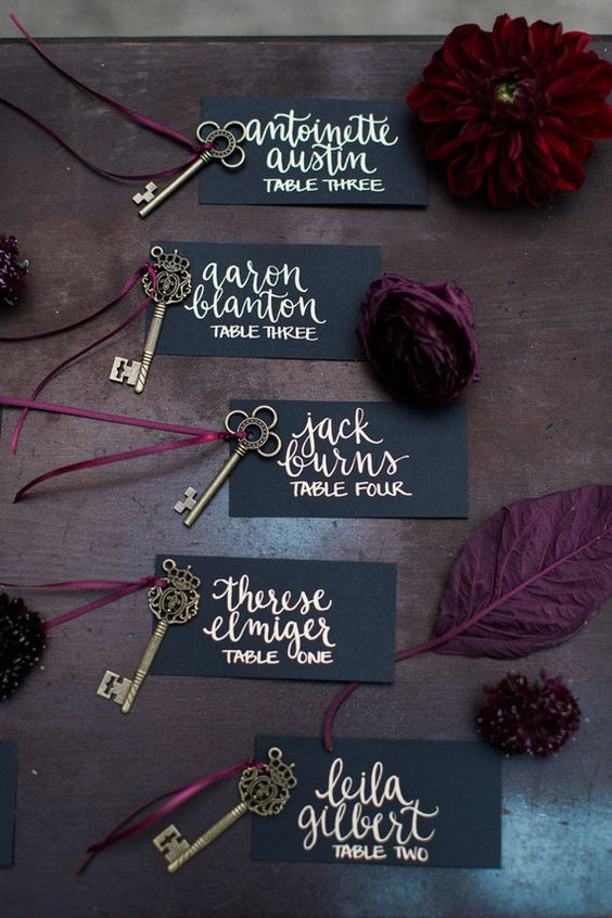 elegant matte black escort cards with gold calligraphy, vintage brass keys and moody blooms