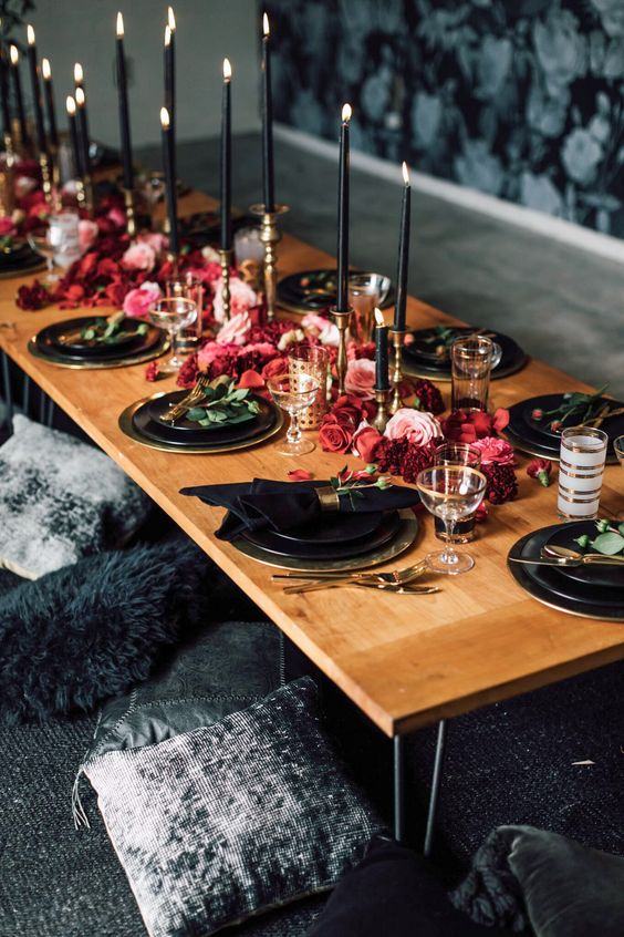a bold wedding tablescape with black candles and plates, hot red and pink blooms on the table