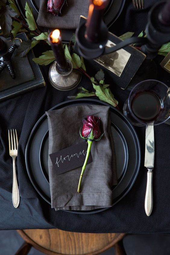 a chic modern black wedding table setting with matte plates, black candles, greenery and a single deep red rose