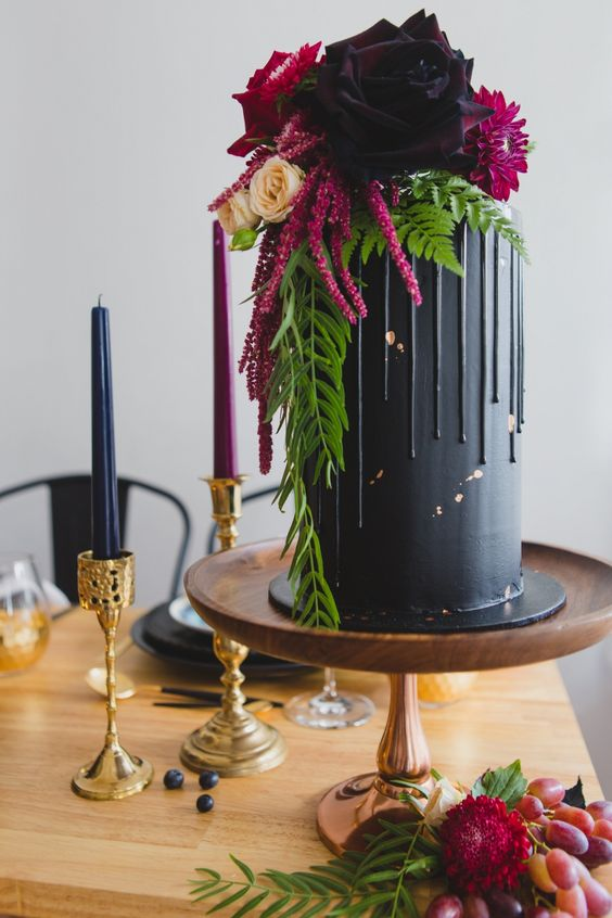 a chic wedding cake in black with drip and with hot red and pink blooms on top