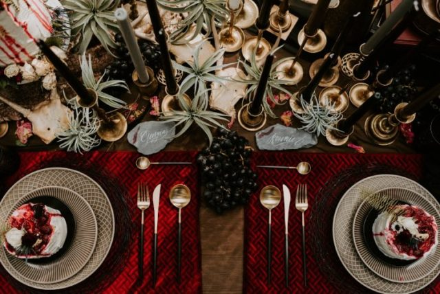 a gorgeous wedding tablescape done in red and black, with woven chargers, grapes, air plants, black candles and gilded touches